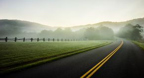 Annebbi il rotolamento attraverso le terre blu dell'azienda agricola della strada panoramica della cresta Fotografia Stock