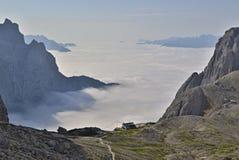 Annebbi il rotolamento su in una valle fra le rocce in montagne - il chalet della montagna è appena sopra la nebbia immagini stock libere da diritti
