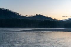 Annebbi in montagne con la foresta ed il fiume sul tramonto fotografia stock