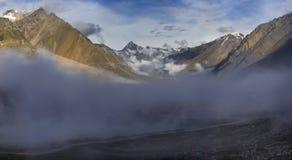 Annebbi nelle alte montagne: le nuvole grige si trovano sotto i picchi colorati livello con neve sui picchi, il giorno di estate  Immagini Stock