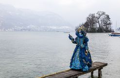 Disguised Person - Annecy Venetian Carnival 2013. Annecy, France, February 23, 2013: Disguised person posing on a pier on Annecy Lake, during a Venetian Carnival Royalty Free Stock Image