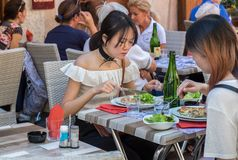 Beautiful asian women with choker necklace eat vegetarian meal in a cafe in Annecy. France royalty free stock photo