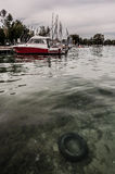 Annecy Lake. Sunken tyre in the the Annecy Lake and anchored yachts Stock Image