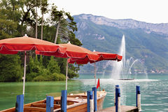 Annecy lake, France with fountain and Alps mountains in the distance Royalty Free Stock Image