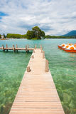 Annecy Lake Pier Crystal Clear. A wooden pier extends into a crystal clear alpine lake near the destination city of Annecy, France Stock Photo