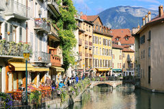 Annecy Old Town. People drink coffee near the River Thiou in Old Town, encircling the medieval palace perched mid-river - the Palais de l'Isle Stock Image