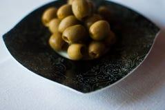 Annerisca il piatto modellato con le olive sulla tovaglia bianca Fotografia Stock Libera da Diritti