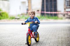 3 années d'équitation d'enfant en bas âge sur son premier vélo Photographie stock