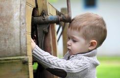 2 années de bébé garçon curieux contrôlant avec le vieil AGR Images libres de droits