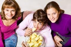 Années de l'adolescence mangeant des chips Images libres de droits