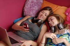 Années de l'adolescence utilisant le téléphone portable et l'ordinateur Image libre de droits