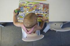 2 anni adorabili del ragazzo di storie di lettura rapida alla biblioteca Fotografia Stock Libera da Diritti