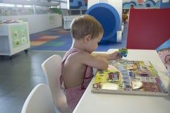 2 anni adorabili del ragazzo di storie di lettura rapida alla biblioteca Fotografia Stock