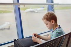 7 anni annoiati del bambino del ragazzo che aspetta il suo aereo Fotografia Stock
