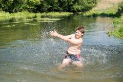 10 anni completi di nuotata del ragazzo in fiume Immagine Stock