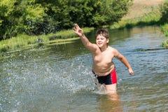 10 anni completi di nuotata del ragazzo in fiume Fotografia Stock