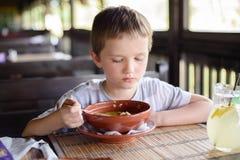7 anni del bambino, ragazzo che mangia minestra Immagini Stock Libere da Diritti