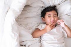 3 anni del piccolo ragazzo asiatico sveglio a casa sul letto, menzogne del bambino Immagine Stock