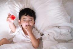 3 anni del piccolo ragazzo asiatico sveglio a casa sul letto, menzogne del bambino Fotografie Stock Libere da Diritti