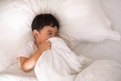 3 anni del piccolo ragazzo asiatico sveglio a casa sul letto, menzogne del bambino Immagini Stock Libere da Diritti