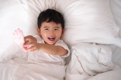 3 anni del piccolo ragazzo asiatico sveglio a casa sul letto, menzogne del bambino Fotografia Stock
