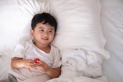 3 anni del piccolo ragazzo asiatico sveglio a casa sul letto, menzogne del bambino Fotografia Stock Libera da Diritti