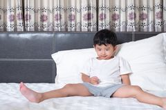 3 anni del piccolo ragazzo asiatico sveglio a casa sul letto, menzogne del bambino Immagini Stock