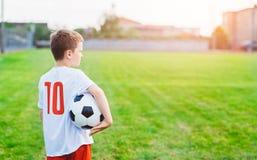 8 anni del ragazzo del bambino della tenuta della palla di calcio Fotografie Stock Libere da Diritti