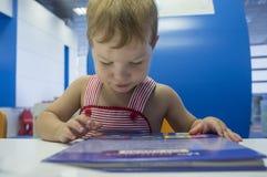 2 anni del ragazzo di storie di lettura rapida alla biblioteca Fotografie Stock