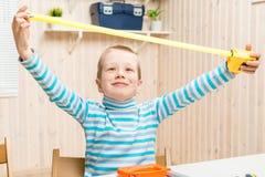 6 anni del ragazzo nel garage con nastro adesivo di misurazione Immagini Stock