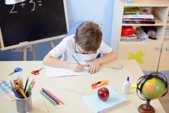7 anni del ragazzo risolve la tavola di moltiplicazione nel suo quaderno Immagini Stock