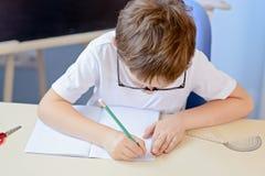 7 anni del ragazzo risolve la tavola di moltiplicazione nel suo quaderno Fotografie Stock Libere da Diritti