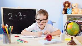 7 anni del ragazzo risolve la tavola di moltiplicazione nel suo quaderno Fotografia Stock Libera da Diritti