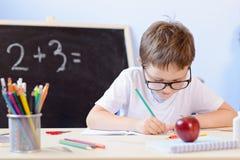 7 anni del ragazzo risolve la tavola di moltiplicazione nel suo quaderno Fotografia Stock