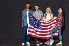 anni dell'adolescenza americani felici con la bandiera degli S.U.A. immagini stock