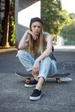 Anni dell'adolescenza in beanie che si siede sul suo pattino fotografia stock libera da diritti