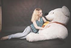 Anni dell'adolescenza biondi svegli nei giochi della camicia di plaid e dei jeans con il suo orso polare dell'orsacchiotto enorme immagini stock