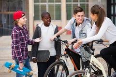 Anni dell'adolescenza che chiacchierano vicino alle bici Immagine Stock