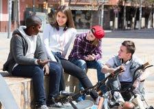 Anni dell'adolescenza che chiacchierano vicino alle bici Immagini Stock