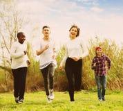 Anni dell'adolescenza che corrono nel parco di primavera Immagine Stock