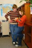 Anni dell'adolescenza che flirtano nella libreria Immagini Stock