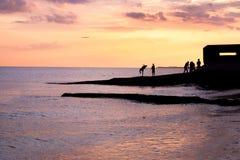 Anni dell'adolescenza che giocano alla spiaggia di Brighton del ob di tramonto Immagine Stock