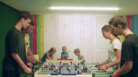 Anni dell'adolescenza che giocano calcio-balilla all'interno, lavoro di squadra in gioco da tavolo, gruppo di calcio della tavola stock footage