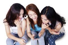 Anni dell'adolescenza che leggono insieme messaggio sul cellulare Fotografia Stock