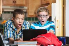 Anni dell'adolescenza colpiti che esaminano computer Immagine Stock Libera da Diritti