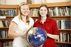 Anni dell'adolescenza delle biblioteche con il globo Immagine Stock