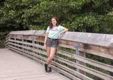 Anni dell'adolescenza di diciassette anni dell'anca che posano su un ponte di legno in Washington Park Arboretum, Seattle, Washin fotografie stock