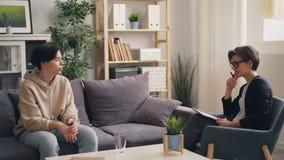 Anni dell'adolescenza emozionali che discutono le difficoltà con il terapista della giovane donna nell'ufficio archivi video