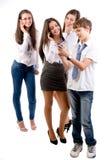 Anni dell'adolescenza facendo uso dei telefoni cellulari Fotografie Stock Libere da Diritti