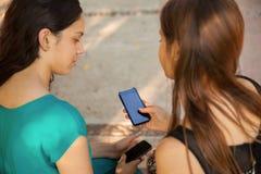 Anni dell'adolescenza facendo uso di un telefono cellulare Fotografia Stock Libera da Diritti